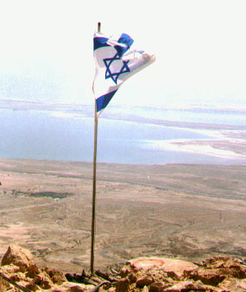 israeli flag with the dead sea view on the background in the judia desert